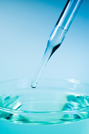 dropper: medicine dropper close up in blue light Stock Photo