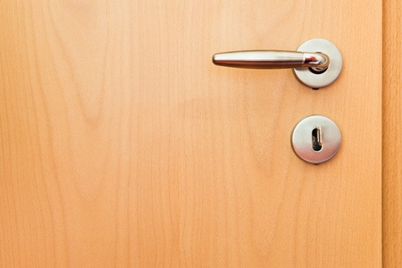door handle: metal handle on wooden door