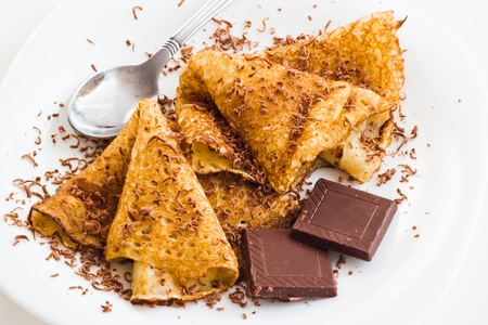 crepes with chocolate and dessert spoon on white table Stock Photo