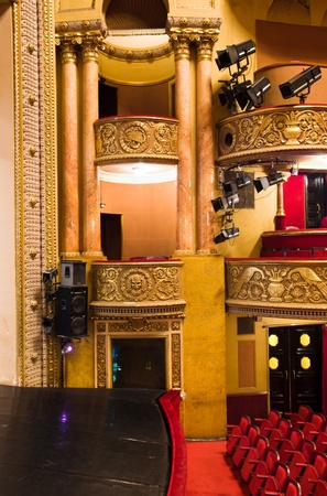 balcony in performance hall with stage lights and chairs photo