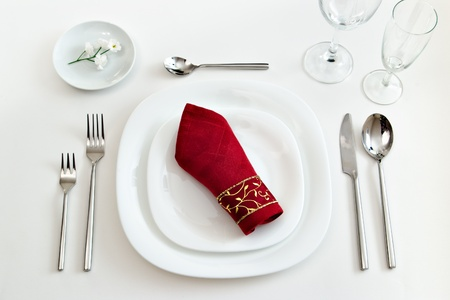 white place setting with dark red napkin photo