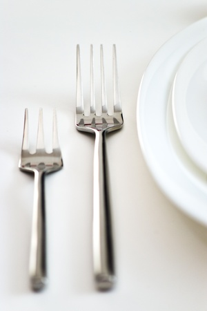 detail of two forks and white plates photo