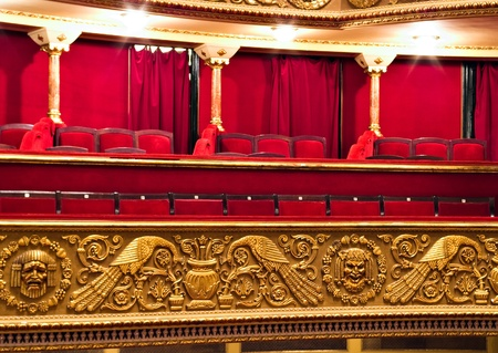 classic theatre balcony with red chairs and golden details