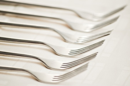 dinnerware: six forks on beige table cloth with shallow depth of field