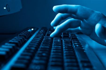 mecanografía: hombre de mano escribiendo en el teclado - azul entonado