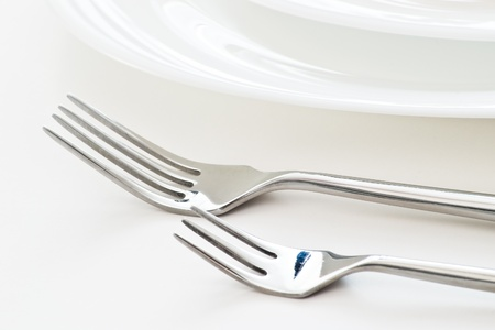 dinnerware: closeup with two forks on white