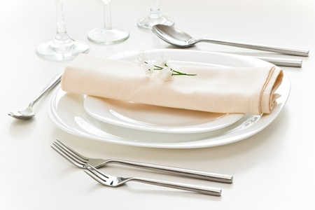 white place setting with beige napkin