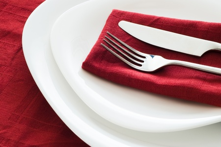 fork and knife on white plates and dark red napkin