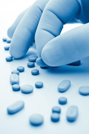 gant blanc: Main dans la main blanche s�lectionnant pilules en teinte bleue Banque d'images