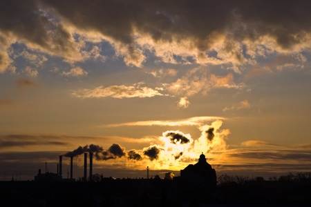 silhouette of industrial smoke and clouds in morning light photo