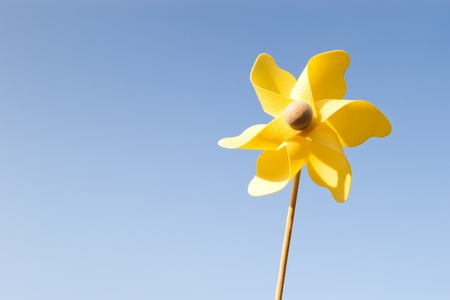 yellow pinwheel on clear blue sky photo