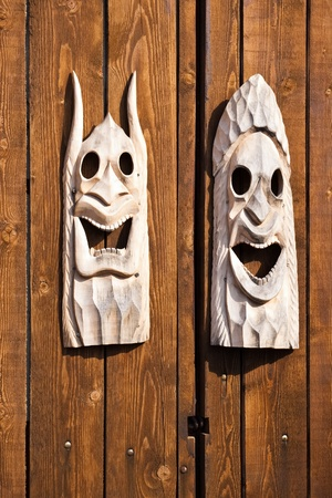 two wooden traditional masks on wood planks Stock Photo - 12826399