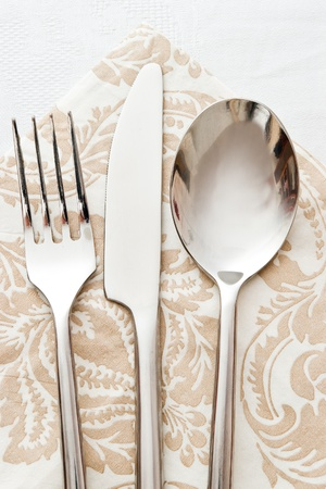 fork spoon and knife on beige napkin photo