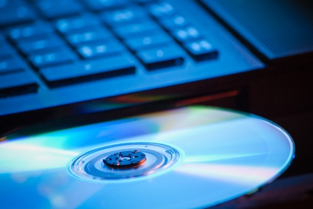 eject: closeup of DVD on laptop in blue light