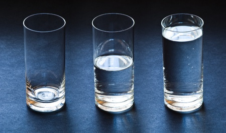 half: three glasses empty half and full with water on dark blue background