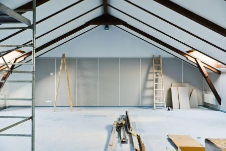 attic renovations with ladder and gray walls Standard-Bild