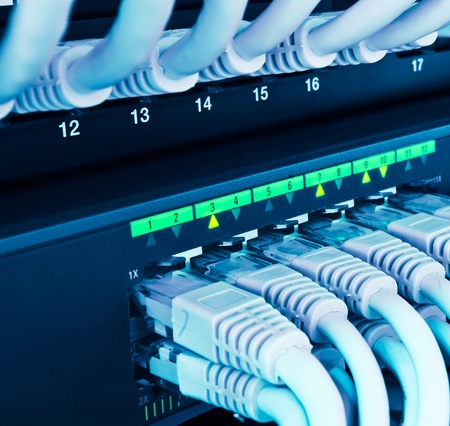 computer networking: closeup of network hub and cables blue toned