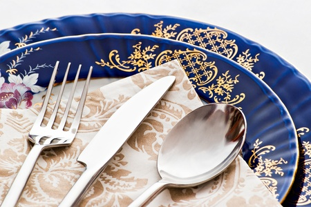 empty plate: fork knife and spoon on blue porcelain Stock Photo