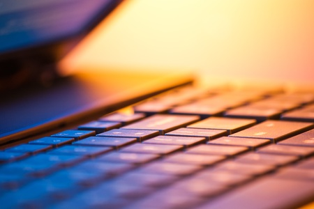 laptop computer detail with copy space and shallow depth of field in warm light