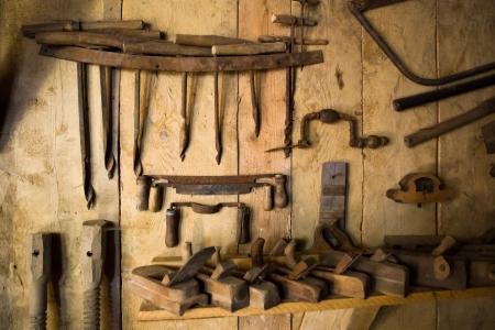 herramientas de carpinteria: muy antiguas herramientas oxidadas para trabajar la madera en la pared