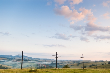 three crosses against  sky and village on hills Stock Photo
