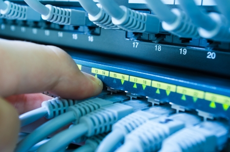 network connection plug: hand plugging or unplugging cable in network switch Stock Photo