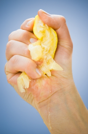 squeeze: hand squeezing lemon on blue background Stock Photo