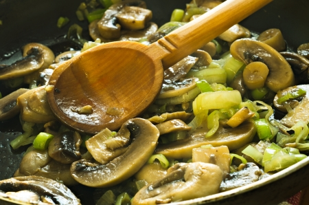 closeup of mushrooms and onions fried in pan and mixed with wooden spoon photo