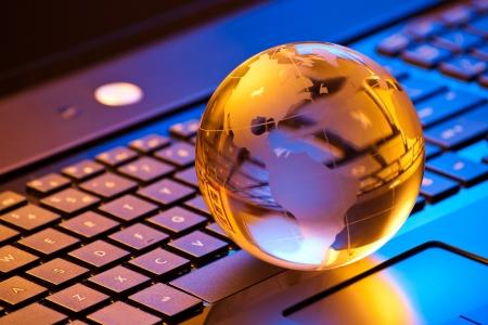 混合光でノート パソコンのキーボードの小さな地球と世界のコンピューター ビジネス コンセプト