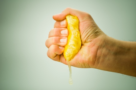squeeze: hand squeezing lemon on green background