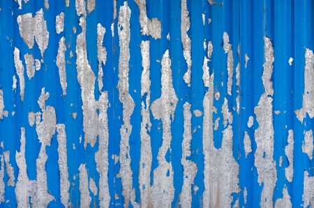 deteriorating: old blue painy peeling from metal surface