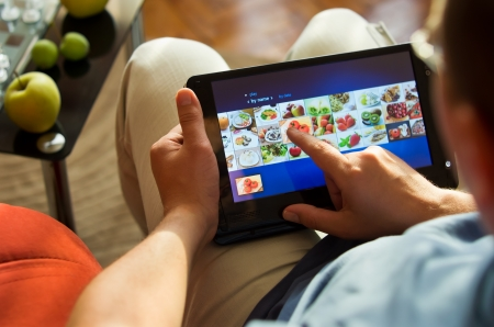man sitting in living room choosing food on touch tablet-pc photo