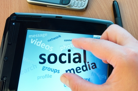 social media and connected words on tablet-pc with fingers touching screen Stock Photo