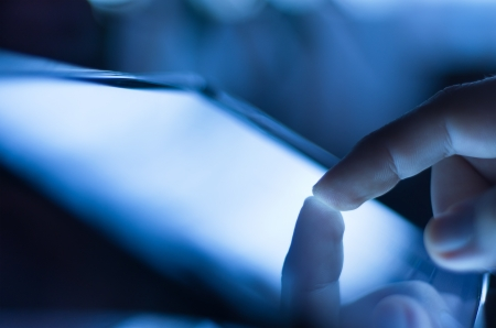 dedo: Primer plano de los dedos tocando la pantalla de tablet-pc con poca profundidad de campo azul entonado Foto de archivo