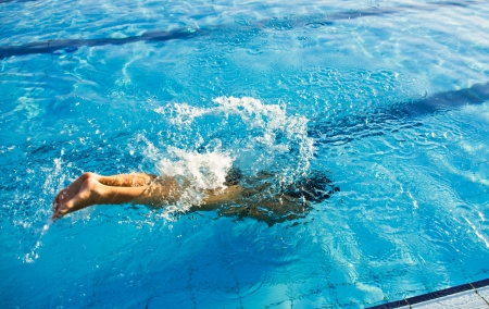 swimmer dive into blue pool