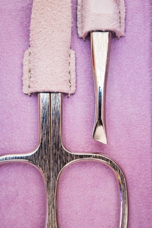 closeup of manicure scissors and pincer on purple leather Stock Photo
