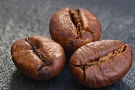 coffeebeans: three coffeebeans on black stone Stock Photo