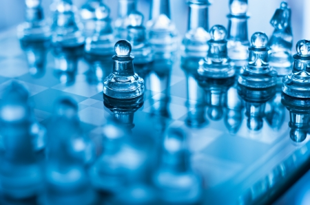 glass chess pawn in front with shallow depth of field in blue light photo