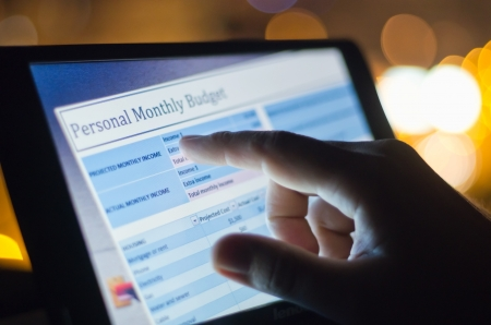 finger touching screen with monthly budget  in city at sunset Banque d'images