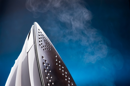 close up of ironing tool emitting steam on blue photo