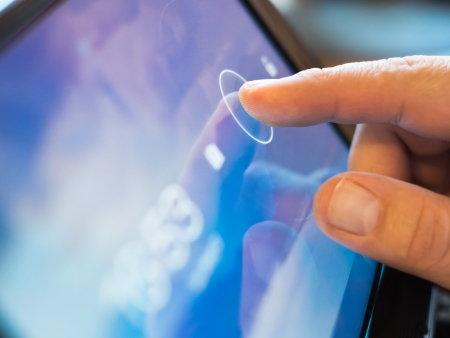 input devices: finger touching screen  on tablet-pc with shallow depth of field