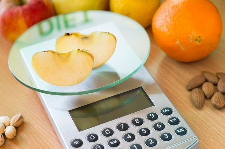 kitchen scale: apple slices on digital kitchen scale and word diet reflected