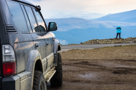 dirty suv and man looking at mountain scenery photo