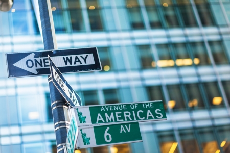 one way sign: one way street signs in New York with glass building in backround Stock Photo