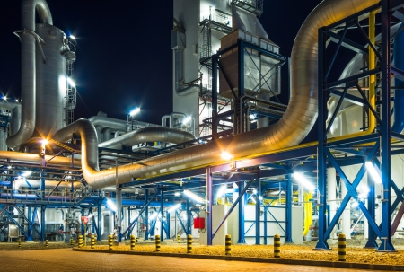 pumps and piping system inside of industrial plant at night