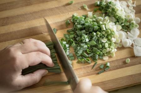 cutting vegetables: cutting green onions on wood board