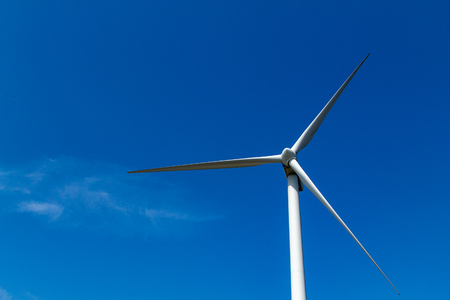 A large windmill in a blue sky for generating environmentally friendly electricity.