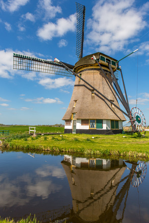A historic windmill in the green fields of Rijpwetering in The Netherlands.