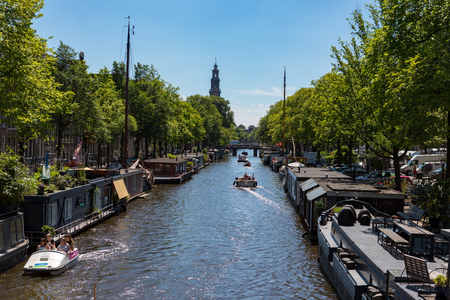Houseboats at the Prinsengracht in the dutch city of Amsterdam on a blue sky sunny day. Redactioneel