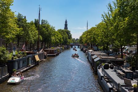 Woonboten in Prinsengracht in de Nederlandse stad van Amsterdam op een blauwe hemel zonnige dag.
